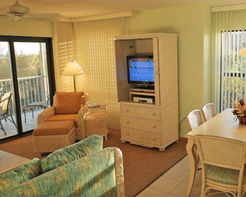 A well furnished living room with television dining area and balcony.