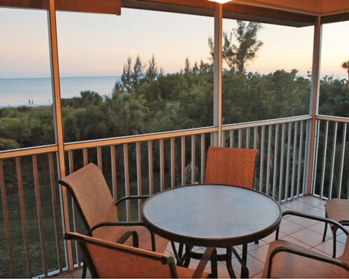 Balcony with patio furniture surrounded by wooded area with beach view.