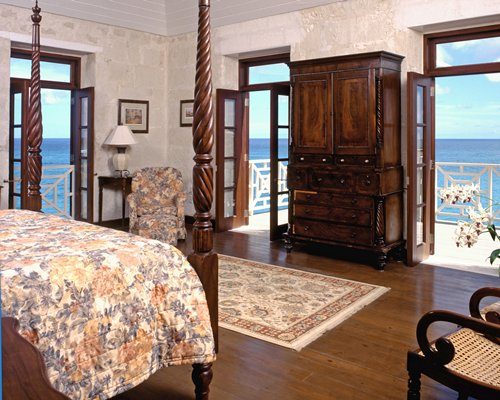 A well furnished bedroom with a king bed and a balcony.