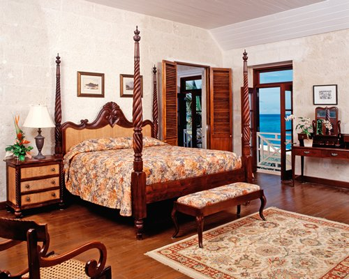 A well furnished bedroom with a king bed and an beach view.
