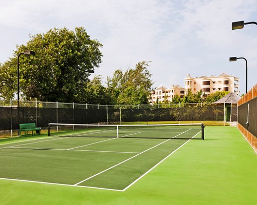 An outdoor tennis court alongside multi story units.