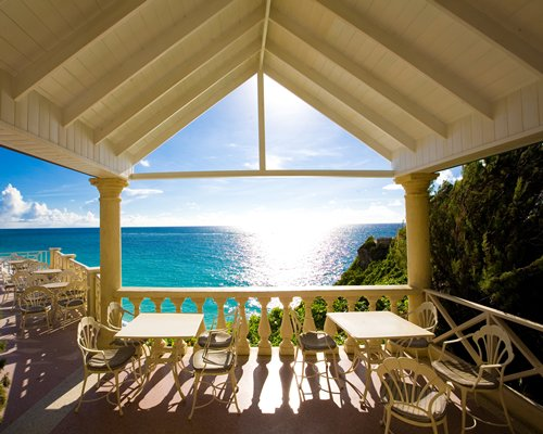 A balcony view of a dining area alongside the ocean.