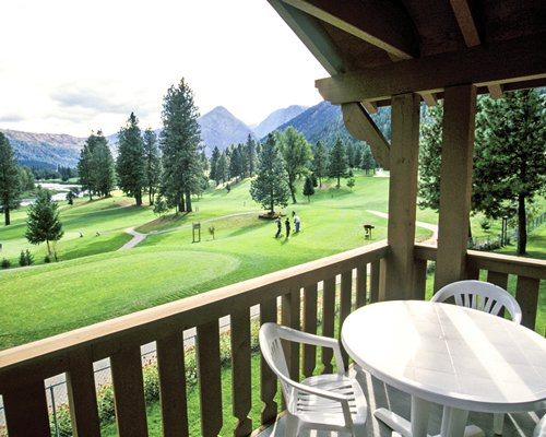 A patio furniture on the balcony alongside the golf course.