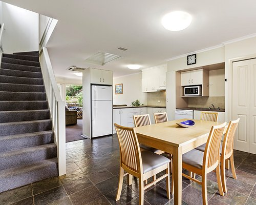 An open plan dining and kitchen area alongside the staircase.