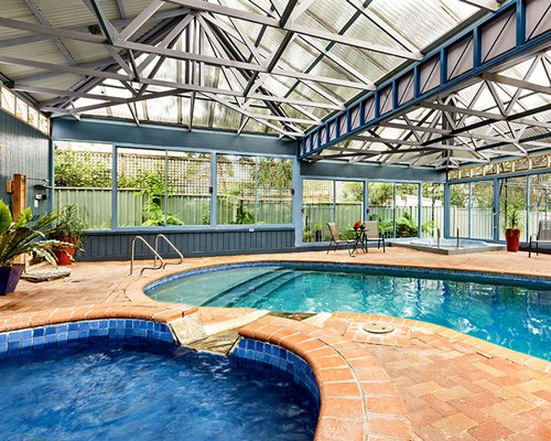 An indoor swimming pool with patio furniture alongside a hot tub.