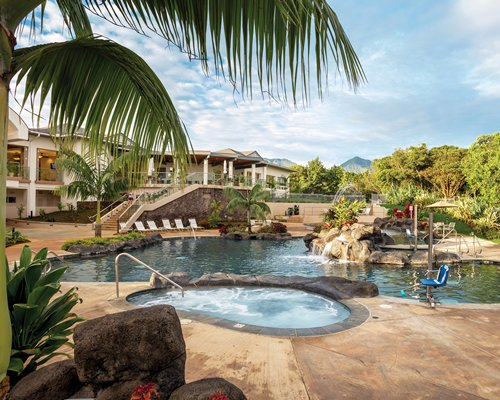 An outdoor swimming pool with a hot tub and chaise lounge chairs alongside resort condos.