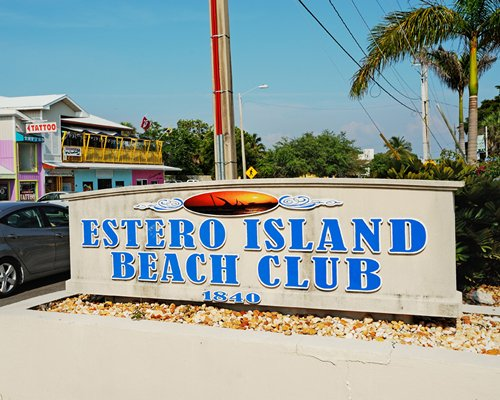 Signboard of Estero Island Beach Club with palm trees.