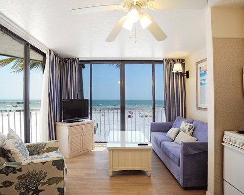 A well furnished living room with a television and ocean view.