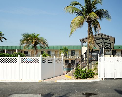 Street view of units at Estero Island Beach Club with a stairway and palm trees.