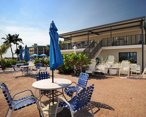Outdoor restaurant with sunshades and stairway to a unit at Estero Island Beach Club.