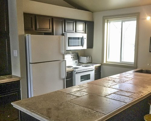 A condo with a queen bed open plan kitchen and dining area.