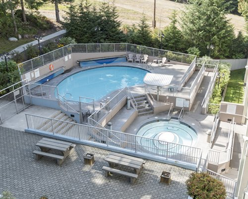 View of multiple unit balconies with an outdoor hot tub and chaise lounge chairs.