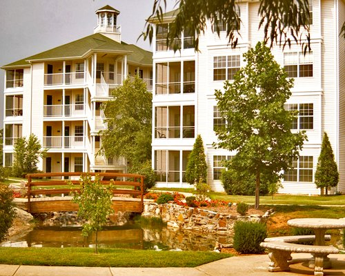 Exterior view of multiple unit balconies with a pathway across the pond.