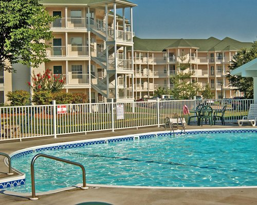 An outdoor swimming pool alongside multi story condos.