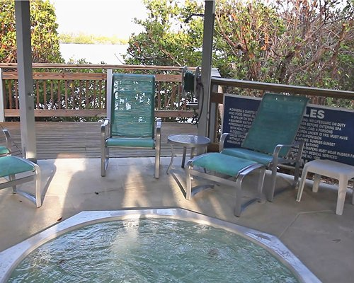 An outdoor hot tub with patio chairs alongside water view.