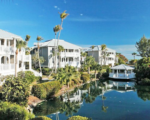 Scenic exterior view of Sanibel Cottages Resort alongside waterfront and covered picnic area.