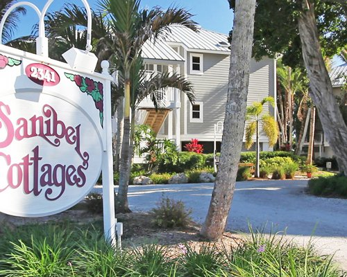 Scenic exterior view of Sanibel Cottages Resort with a signboard.