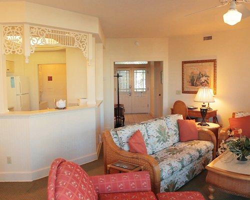 A well furnished living room alongside kitchen.