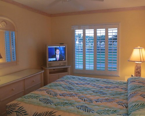 A well furnished bedroom with king bed and a television.