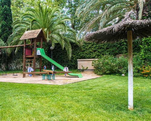 Playground with kids play scape and thatched sunshade.