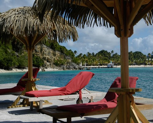 A view of chaise lounge chairs and thatched sunshades alongside the beach.