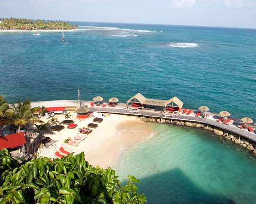 An aerial view of the beach with wooden pathway chaise lounge chairs and thatched sunshades alongside the sea.