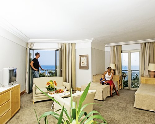 Family at a furnished unit with a bed couch television and sea view.