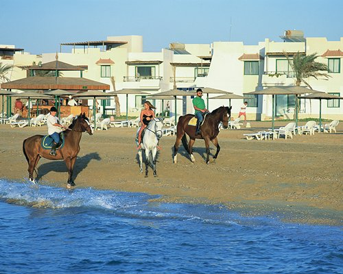People riding horses on the beach alongside the resort.