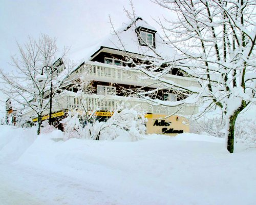 An exterior view of the Adler Bellevue Ferienclub E.V resort covered by snow.