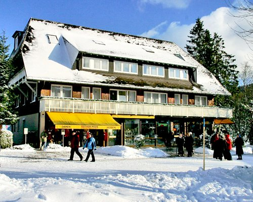 A street view of Adler Bellevue Ferienclub E.V. resort covered in snow.