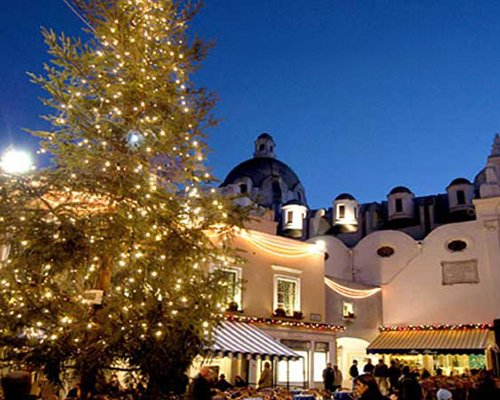 View of festively decorated Hotel Villa Igea at dusk.