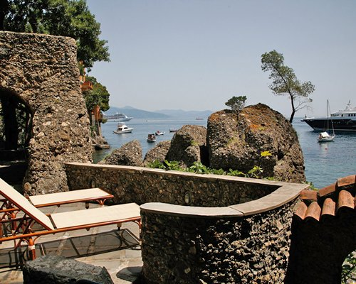 Balcony view of the sea with chaise lounge chairs.