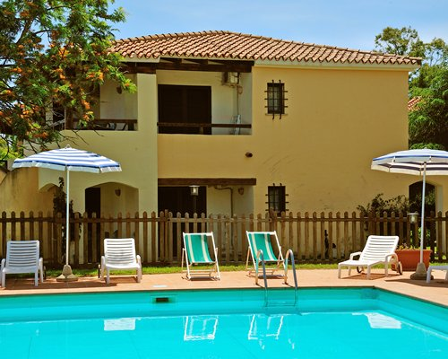 A unit with outdoor swimming pool sunshades and chaise lounge chairs.