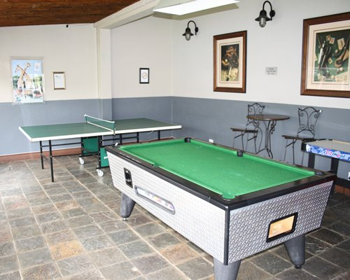 Indoor recreation room with pool table and ping pong.