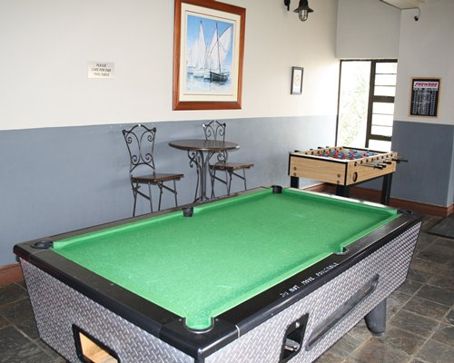An indoor recreational room with pool table and foosball table.