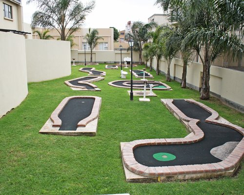 Outdoor recreation area with putt putt golf course and palm trees.