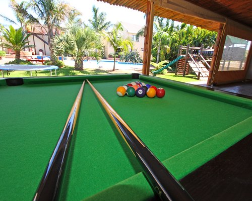 Indoor recreation room with pool table and outside playground.