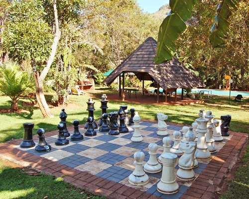 An outdoor recreational area with a giant chess set on the lawn.