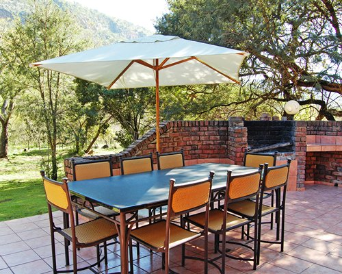 Scenic outdoor dining area with barbecue grill and sunshade.
