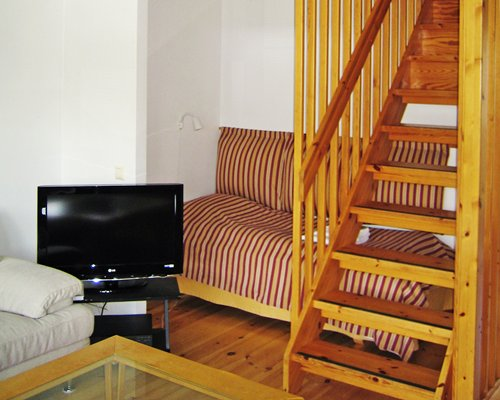 A well furnished living room with television and wooden stairway.