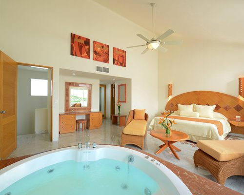 A large well furnished bedroom with a hot tub.