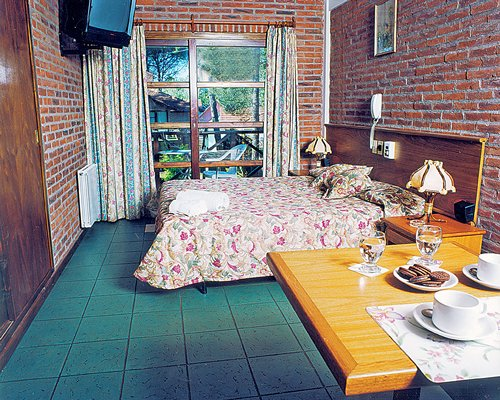 A well furnished bedroom with dining area and outside view.