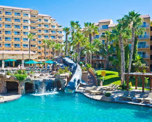 Outdoor swimming pool with a water slide at Villa del Palmar Cabo San Lucas.