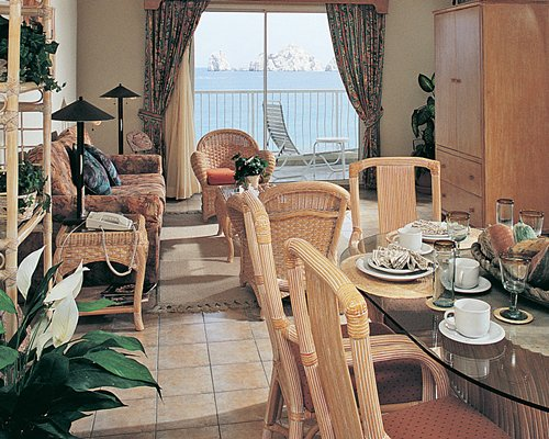 A living room with open plan dining area and balcony with ocean view.
