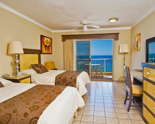 A well furnished bedroom with two beds and an ocean view.