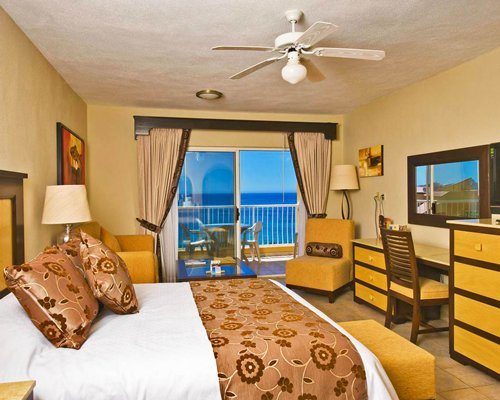 A well furnished bedroom with two twin beds and balcony with an ocean view.