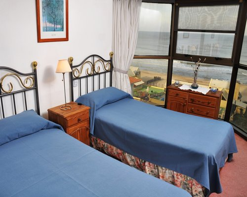 A well furnished bedroom with two twin beds and ocean view.