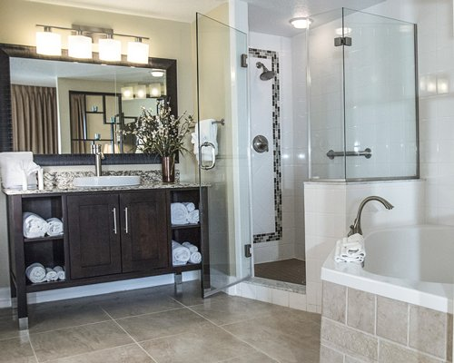 A bathroom with bathtub shower stall and closed sink vanity.