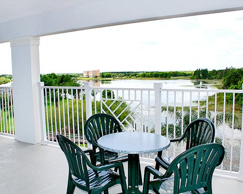 A balcony view of a waterfront with patio furniture.
