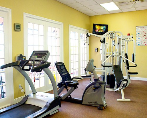 A well equipped indoor fitness center with a television.